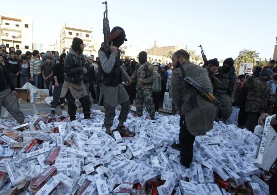 Fighters from Islamic State in Iraq and the Levant hold their weapons as they stand on confiscated cigarettes before setting them on fire in the city of Raqqa