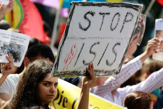 A Kurdish protester of the Yazidis ethnic minority holds a placard against Islamic State militants during a demonstration in Frankfurt