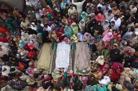 Relatives gather beside the bodies of victims who were killed in yesterday's suicide bomb attack on the Wagah border, before funeral prayers in Lahore