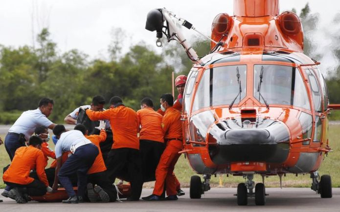 Indonesian Search and Rescue crews unload one of two bodies of AirAsia passengers recovered from sea at the airport in Pangkalan Bun, central Kalimantan