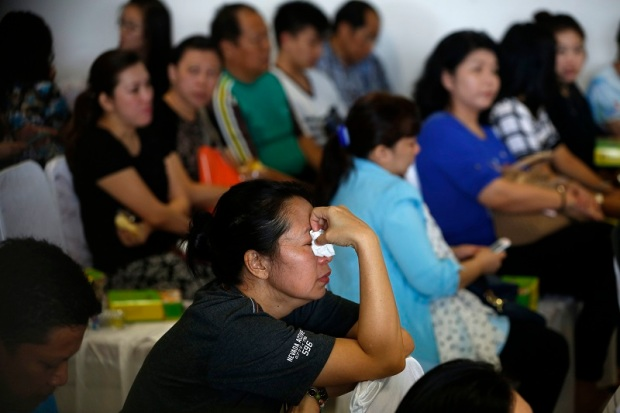 Family members of passengers onboard missing AirAsia flight QZ8501 react as they await news in Juanda International Airport, Surabaya