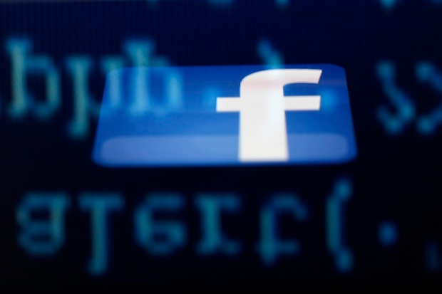 A Facebook logo on an Ipad is reflected among source code on the LCD screen of a computer in this photo illustration