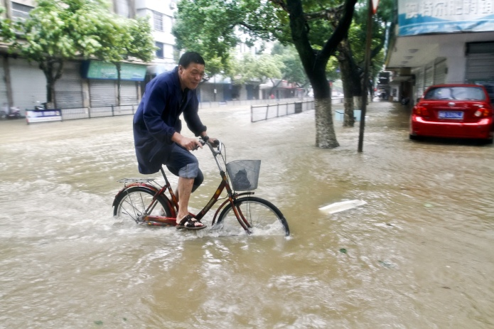 (150711) -- NINGBO, July 11, 2015 (Xinhua) -- A resident rides on a road submerged by water in Xiangshan County of east China's Zhejiang Province, July 11, 2015. The approaching Typhoon Chan-Hom was moving slower on Saturday morning and it's now forecast to either make landfall between noon and evening in east China's Zhejiang Province or just pass through.  (Xinhua/He Yousong) (zwx)