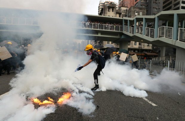 An anti-extradition bill protester tries to extinguish a tear-gas cannister, on July 27, in Yuen Long. Photo Sam Tsang
