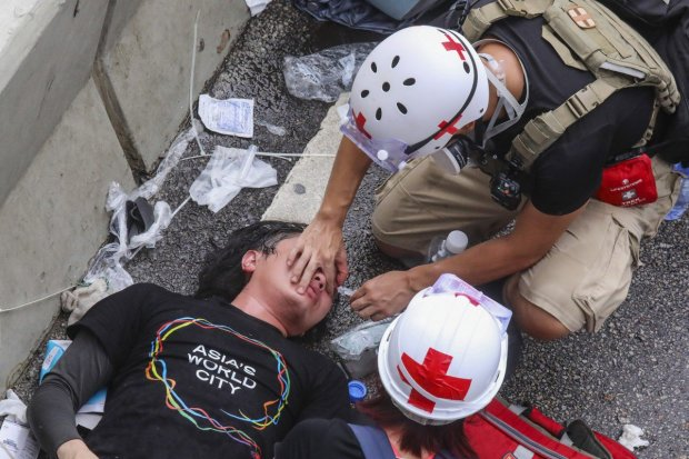 An injured protester is treated after clashing with police on July 1, 2019. Photo K. Y. Cheng.jpg