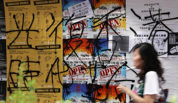 """Graffiti reading """"Liberate Hong Kong. Revolution of our time"""" is seen on a wall of posters in the Sheung Wan district. Photo K.Y. Cheng"""